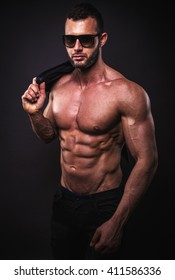 Muscular and fit male model posing in studio.
