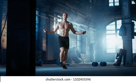 Muscular Fit Man Exercises with Jump / Skipping Rope in a Deserted Factory Hardcore Gym. He's Sweaty from His Cross Fitness Exhausting Training.