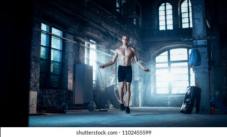 Muscular Fit Man Exercises with Jump / Skipping Rope in a Deserted Factory Hardcore Gym. He's Sweaty from His Cross Fitness Exhausting Training. Cold ambient.