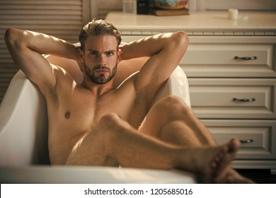 Muscular and fit man relaxing in luxury bathtub.