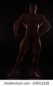 Muscular and fit young bodybuilder fitness male model posing over black background
