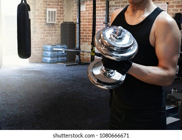 Muscular Fitness Asian man holding dumbbell in hand in training at gym.Weight fit bodybuilder strong for biceps,triceps and shoulder. Concept of healthy lifestyle and sport.