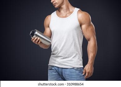 Muscular fitness male bodybuilder holding protein shake bottle ready for drinking. Studio shot on dark background.