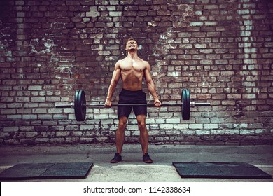 Muscular fitness man doing deadlift a barbell over his head in outdoor, street gym. Functional training. Snatch exercise.