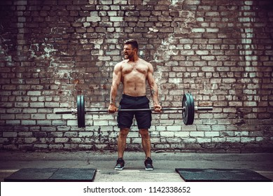 Muscular fitness man doing deadlift a barbell over his head in outdoor, street gym. Functional training. Snatch exercise