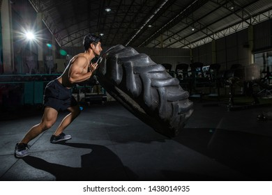 Muscular fitness shirtless man moving large tire in gym center, concept lifting, workout cross training