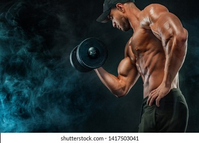 Muscular fitness sports man, atlete with dumbbell in fitness gym.