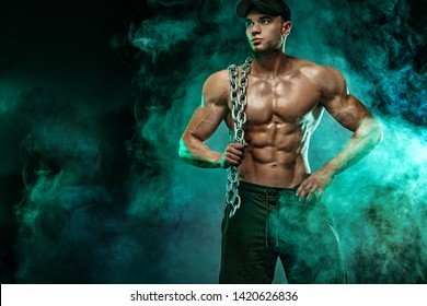 Muscular fitness sports man, atlete with chains in fitness gym.