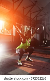 Muscular fitness woman deadlift a barbell over his head crossfit in the gym. Sports, crossfit and fitness - concept of healthy lifestyle. Woman in the fitness club. Crossfit woman. Crossfit style