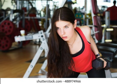 Muscular fitness woman doing exercises. Image of fitness woman in red sports clothing. girl in the gym. sport, fitness, gym and lifestyle - concept of healthy