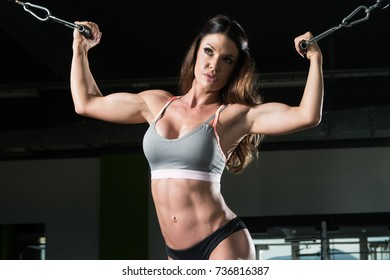 Muscular Fitness Woman Doing Heavy Weight Exercise For Biceps On Machine With Cable In The Gym