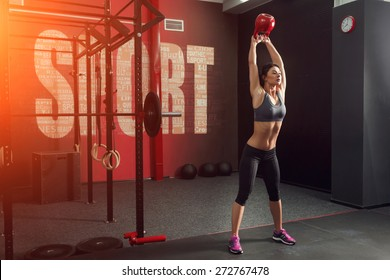 Muscular fitness woman, holds up a red kettlebell crossfit the gym. Sports and fitness - concept of healthy lifestyle. Fitness woman in the gym. Crossfit woman. Crossfit style. Crossfit and fitness
