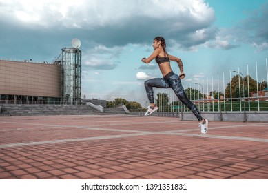 Muscular girl runs in the summer in the city, on a morning jog, high jump. Sportswear leggings top. Phone earphones. Fitness concept jogging, lifestyle. Free space for text.