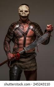 Muscular gladiator in skull mask holding sword