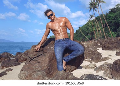 Muscular gorgeous sexy fitness wet young man with athletic body and naked torso in blue jeans wearing sunglasses sitting on rocks on the beach. Athletic tanned male model enjoying vacation