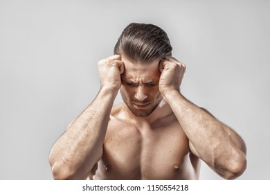 Muscular guy holding his head having strong tension headache. Young man suffering from head migraine, feeling pressure, tension and stress. Healthcare, medical and sickness concept. Vertigo, hangover.