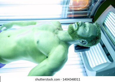 Muscular guy lying on his back in a sunbed, skin tanning concept