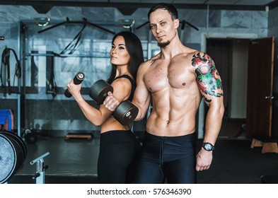 Muscular guy and sports girl in the gym training . Naked press , inflated muscles . Athletes hold weights . The guy with the tattoo on his arm and blue eyes girl Asian Korean