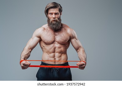 Muscular guy stretching rubber resistance bands in gray background