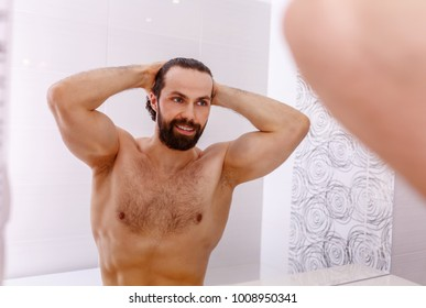 Muscular handsome bearded shirtless man admires a front of the mirror in the bathroom