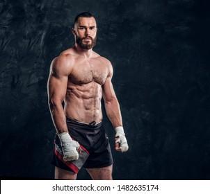 Muskulatur gut aussehender Kämpfer mit nacktem Torso demonstriert seine Macht im Dunkelfoto-Studio.