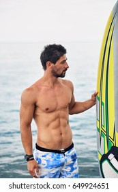 Muscular handsome man holding surfboard. Sea background.