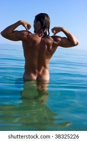 Muscular handsome man relaxing in the sea and showing his biceps
