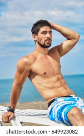 Muscular handsome man sitting on lounger