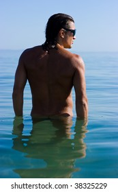 Muscular handsome man in sunglasses relaxing in the sea
