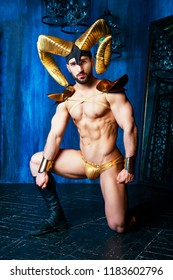 muscular handsome man  wearing a stage costume with big golden horns in the studio