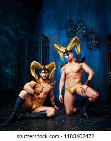 muscular handsome men  wearing a stage costume with big golden horns in the studio
