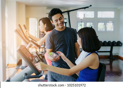 muscular handsome personal trainer man giving bottle water to young asian woman slim body with towel and exercising his legs cardio training on bicycle in fitness gym, lifestyle and sport concept