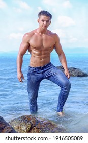 Muscular handsome sexy fitness wet young man with athletic body and naked torso in blue jeans posing outdoors at the beach. Athletic tanned male model enjoying vacation