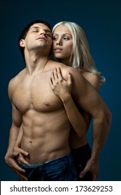 muscular handsome sexy guy with pretty woman, on dark blue  background, glamour  light