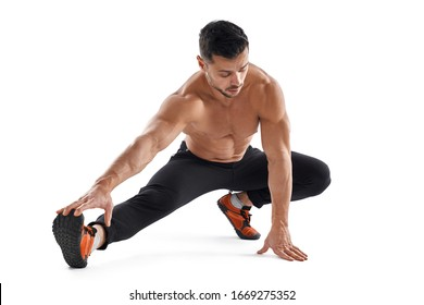 Muscular handsome shirtless man stretching legs on floor isolated on white background. Front view of young caucasian tensed bodybuilder posing in studio. Concept of sport, healthy lifestyle.