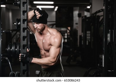 Muscular handsome strong athletic bodybuilder fitness model posing after exercises in gym on diet