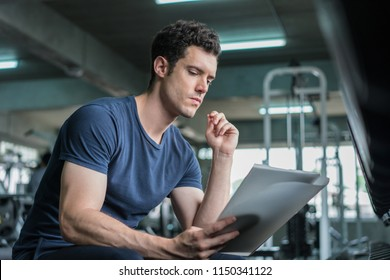Muscular handsome trainer looking at fitness plan on clipboard for working out in the fitness gym.