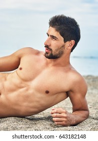 Muscular handsome young man with naked torso lying on the beach. Sea background.