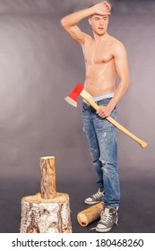 Muscular handsome young man in paint spattered jeans, sneakers and a bare chest standing chopping logs with an axe on a grey studio background / Muscular young man chopping logs
