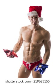 Muscular handsome young man in a speedo and Santa Claus hat standing holding two colorful festive Christmas gifts to celebrate the season, on white