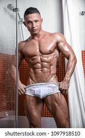 Muscular handsome young sexy wet naked man posing in shower in white underwear