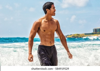 Muscular Hawaiian man walking on the beach as ocean waves crash behind him