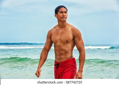 Muscular Hawaiian man walking on the beach
