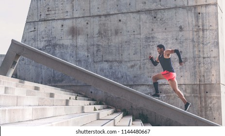 Muscular hispanic dark-skinned male athlete build running up a flight of stairs with speed.Concret background wall with copy space area for text message or advertising content