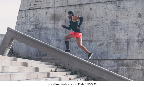 Muscular hispanic Young male dark-skinned athlete running up a flight of stairs with speed, sporty young man in black t-shirt training or working out outdoors while jogging up the steps.