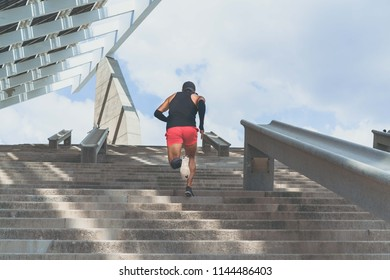 Muscular hispanic Young male dark-skinned athlete running up a flight of stairs with speed, sporty young man in black t-shirt training or working out outdoors while jogging up the steps. Rear view