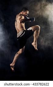 Muscular kickbox or muay thai fighter punching in jump. Smoke.