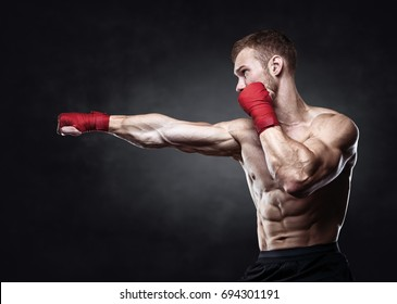 Muscular kickbox or muay thai fighter punching.