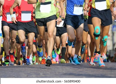 muscular legs of a large number of runners during sports race