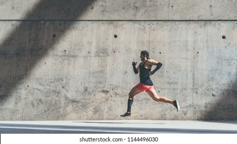 Muscular Male athlete sprinter running fast,exercising outdoors,jogging outside against gray concret background with copy space area for text message or advertising content.Side view,full length.Wide